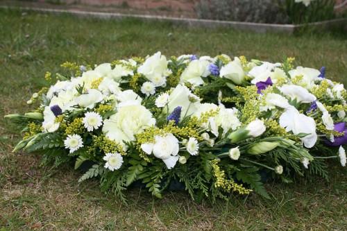 地面に置かれた白いバラ、ガーベラ、トルコききょうなどのフラワーアレンジ