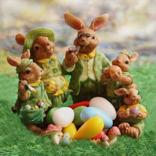 イースターエッグを持つ服をきたウサギの一家