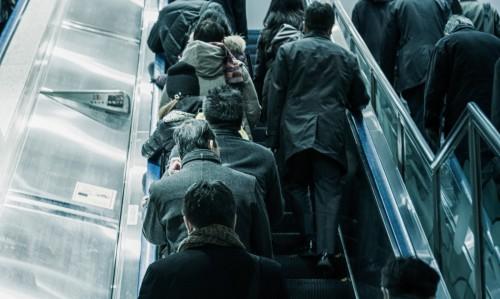 ぎっしりと通勤客が左側に整列している東京のエスカレータ