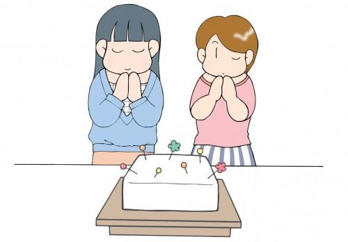 大きな豆腐に待ち針を刺して手を合わせる女性2人