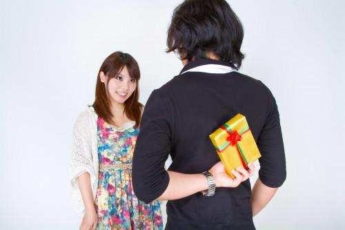 女性を目の前にして背後にプレゼントを隠し持つ男性