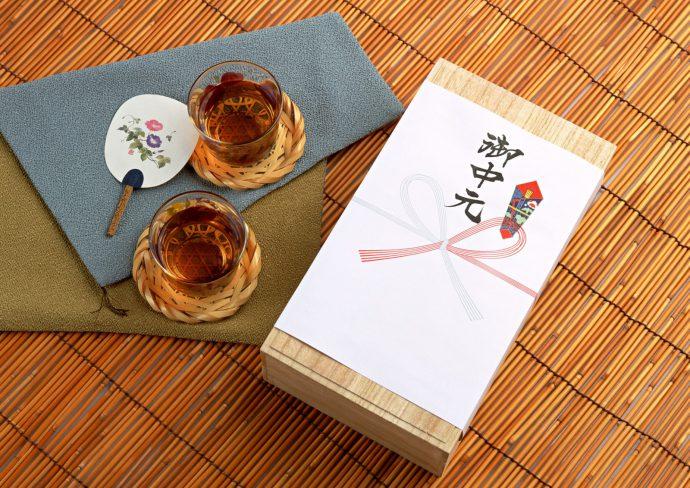 お中元ののし紙が掛けられた箱とコップに入った麦茶