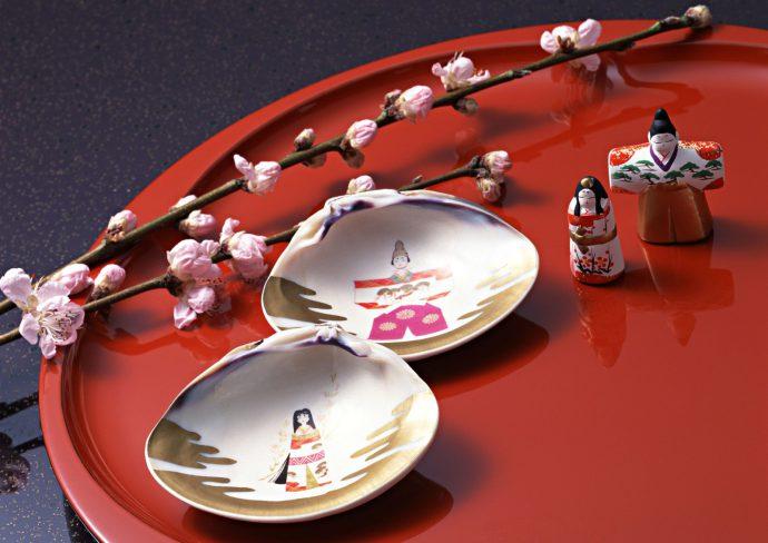 立ち雛と貝殻の裏に描かれたお雛さまと桃の花が置かれている