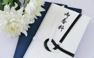 「御香料」と書かれた香典袋と白い菊の花が2輪ある写真