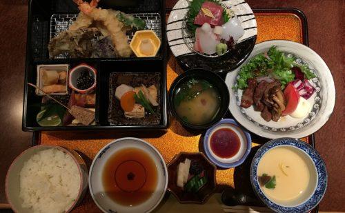 揚げ物・煮物・口取り・向付けの入った松花堂弁当の写真。刺身・ご飯・香の物は別の椀に入っている。