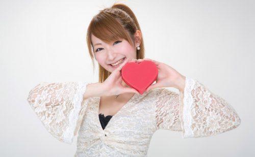笑顔でハート型のオブジェを持つ女性の写真
