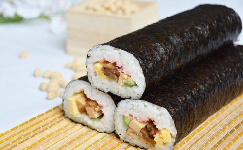 厚焼き卵、しいたけ、高野豆腐、胡瓜、かんぴょうを巻いた巻寿司が3本積み重ねられている写真