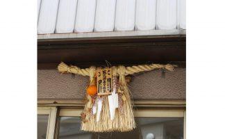 「蘇民将来子孫家門」の護符が付いた注連飾りが玄関にかかっている写真