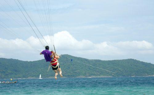 タイのコーラル島にて、海の上をパラセーリングで飛行するインストラクターとお客さんの写真