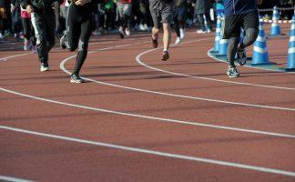 陸上競技場のトラックを走る市民ランナーたちの足元の写真