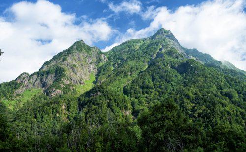 夏の上高地の明神岳。青空と深い緑色の山の写真